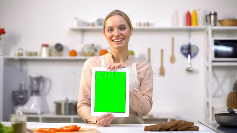 Beautiful girl holding tablet with green screen, easy cooking mobile application stock photos