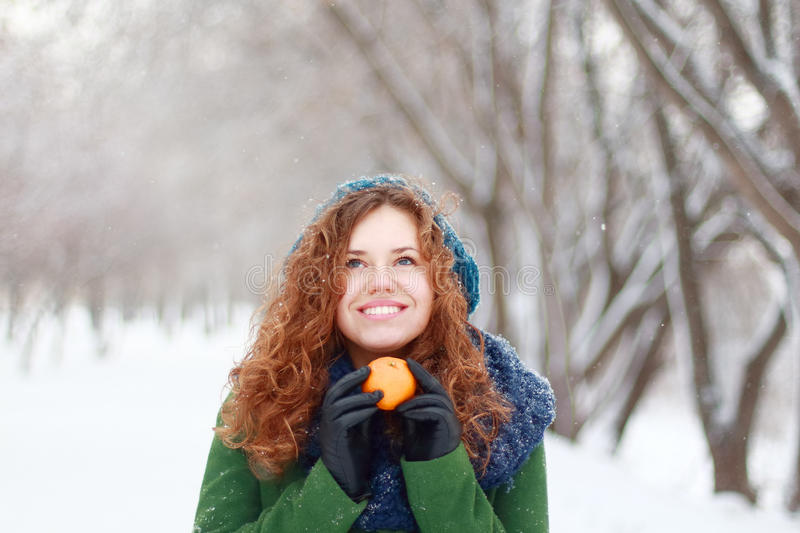 Beautiful girl holds mandarin and looks up at wint. Beautiful girl in blue beret holds mandarin and looks up at winter day in park royalty free stock images