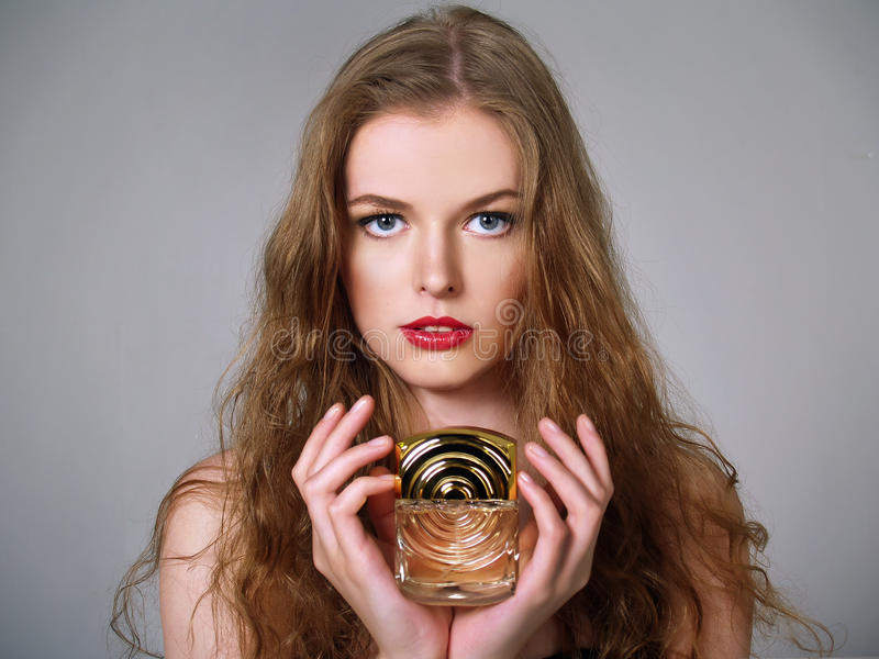 Beautiful girl holds perfumes stock photos