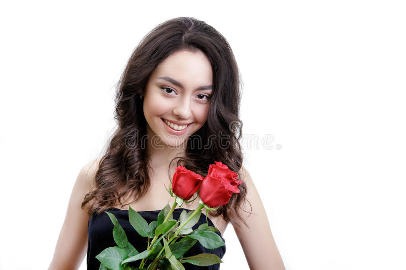 Beautiful girl holds three red roses. She is looks at the camera and smiling. Girl is white with bushy brown hair. Isolated on white background stock image
