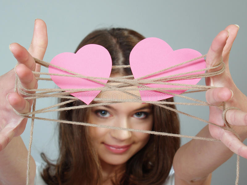 Beautiful girl holds two pink hearts in her hands royalty free stock image
