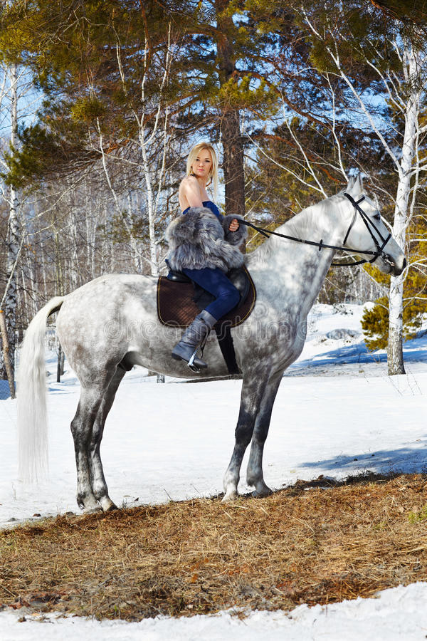 Beautiful girl with horse. Outdoor portrait of beautiful blonde girl in furs with pale horse in sunny winter forest stock images