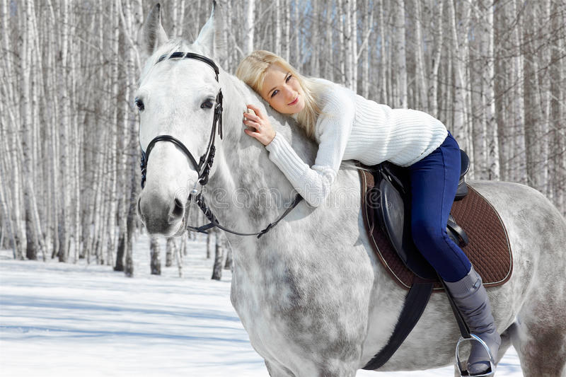 Beautiful girl with horse. Outdoor portrait of beautiful blonde girl sitting on pale horse in sunny winter forest stock photos