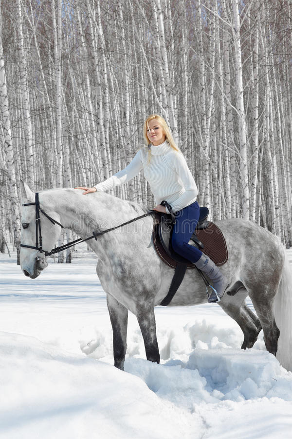 Beautiful girl with horse. Outdoor portrait of beautiful blonde girl sitting on pale horse in sunny winter forest stock image