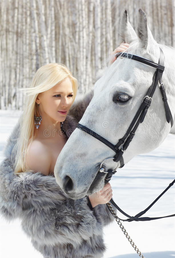 Beautiful girl with horse. Outdoor portrait of beautiful blonde girl with pale horse in sunny winter forest stock images