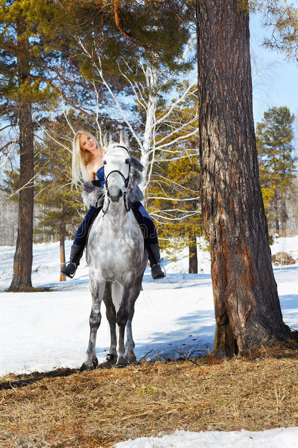 Beautiful girl with horse. Outdoor portrait of beautiful blonde girl in furs with pale horse in sunny winter forest royalty free stock images