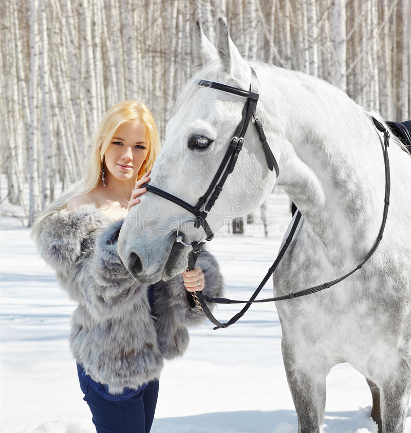 Beautiful girl with horse. Outdoor portrait of beautiful blonde girl with pale horse in sunny winter forest stock photos