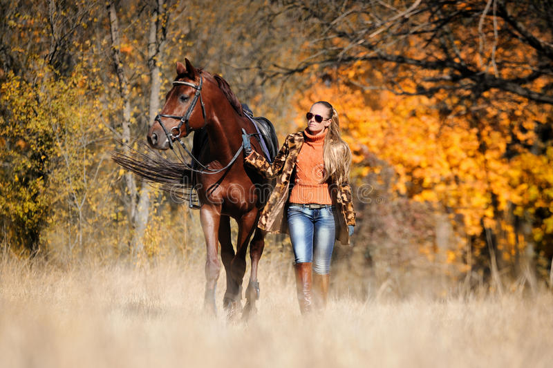 Beautiful girl with horse in autumn forest stock photo