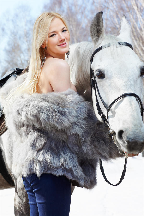 Beautiful girl with horse. Outdoor portrait of beautiful blonde girl in furs with pale horse in sunny winter forest royalty free stock image