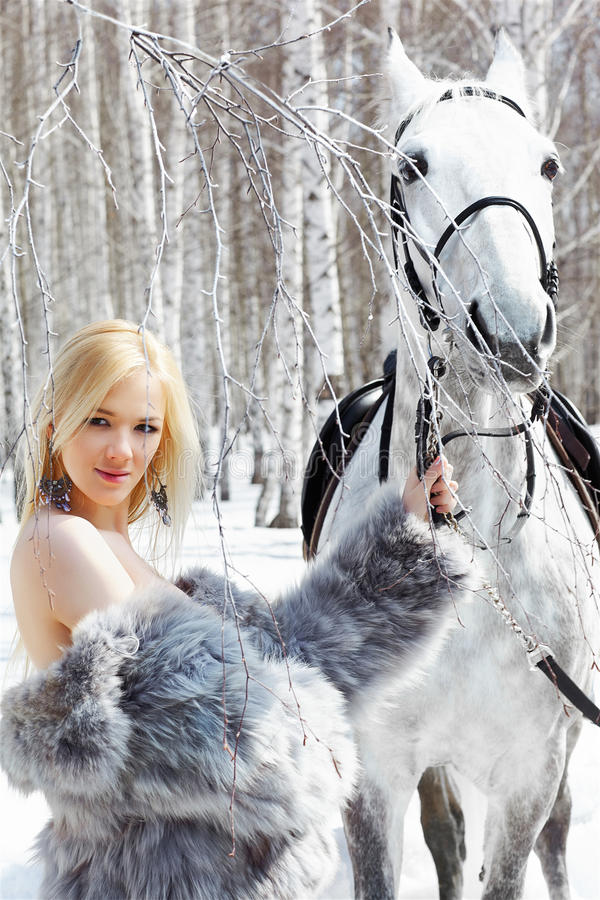 Beautiful girl with horse. Outdoor portrait of beautiful blonde girl with pale horse in sunny winter forest royalty free stock images