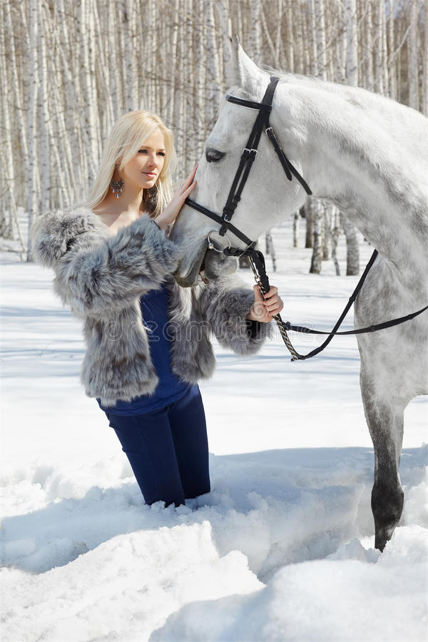 Beautiful girl with horse. Outdoor portrait of beautiful blonde girl with pale horse in sunny winter forest stock photo