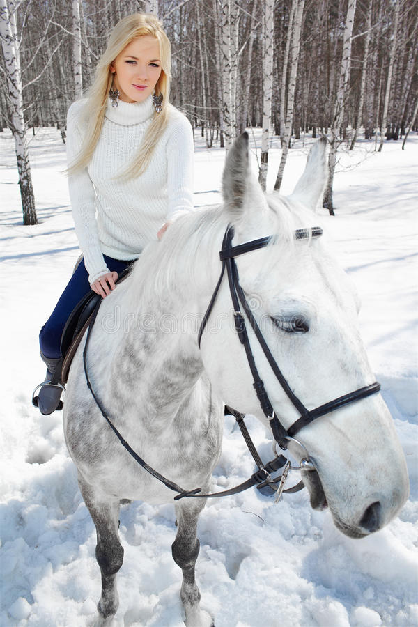 Beautiful girl with horse. Outdoor portrait of beautiful blonde girl sitting on pale horse in sunny winter forest royalty free stock photo