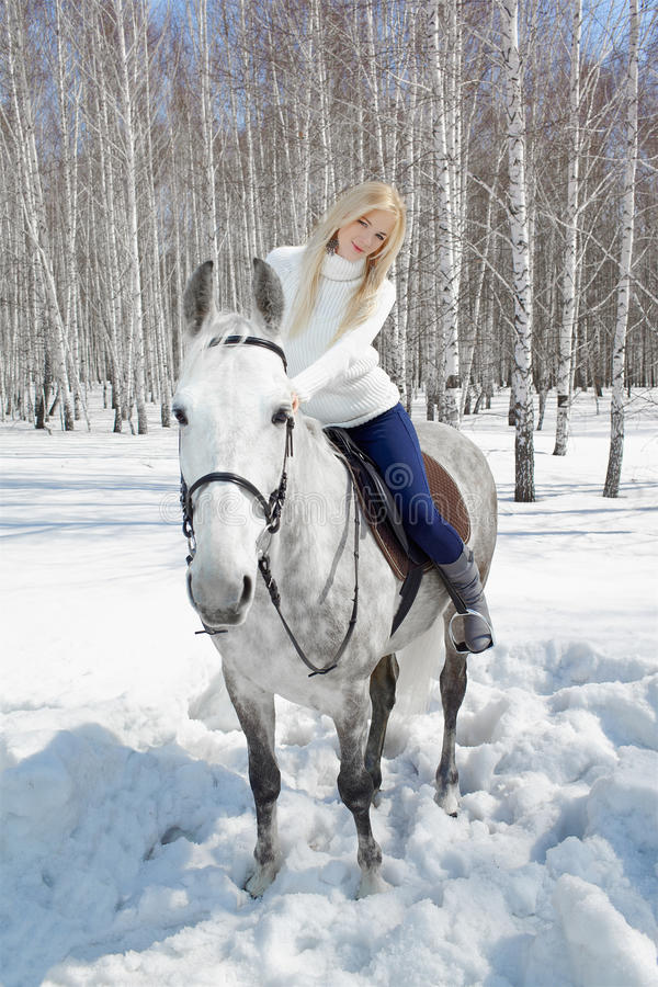 Beautiful girl with horse. Outdoor portrait of beautiful blonde girl sitting on pale horse in sunny winter forest royalty free stock photos