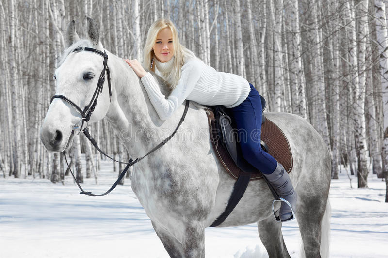Beautiful girl with horse. Outdoor portrait of beautiful blonde girl sitting on pale horse in sunny winter forest royalty free stock image