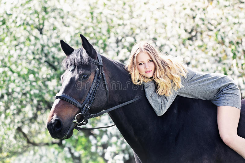Beautiful girl and horse in spring garden royalty free stock photography
