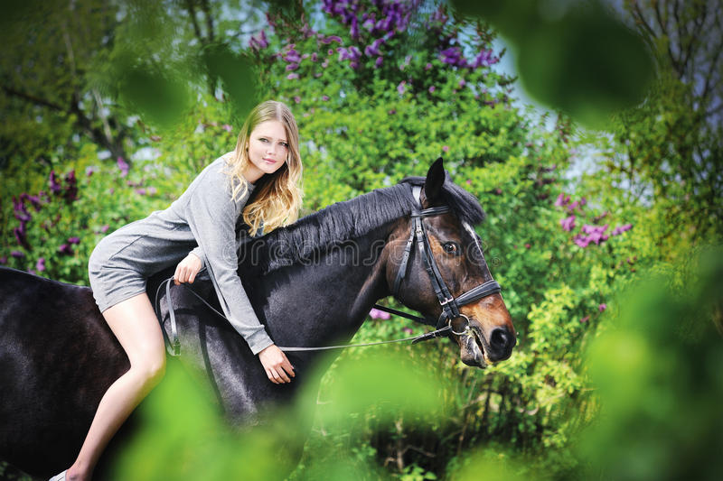 Beautiful girl and horse in spring garden stock images