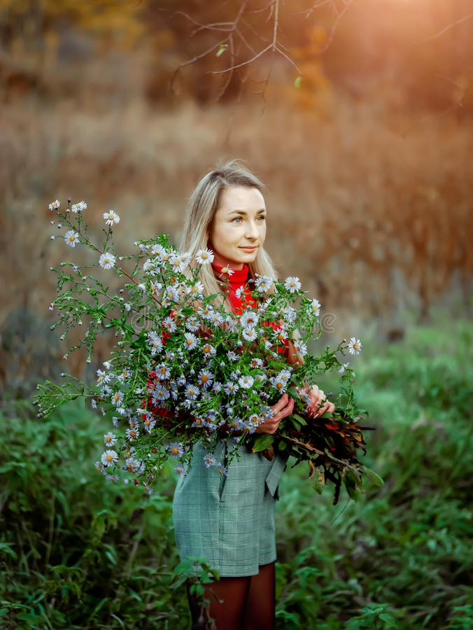 Beautiful girl with a huge bouquet of flowers stock photography