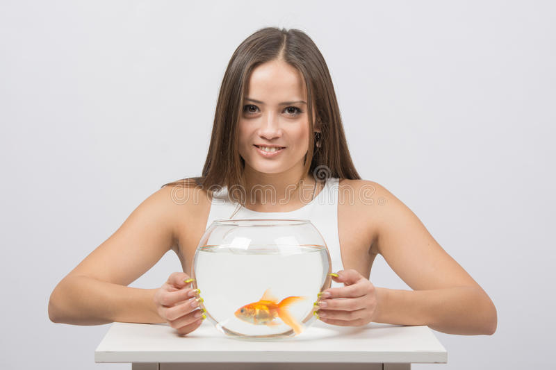 Beautiful girl hugged an aquarium with goldfish. A young girl sits next to a round aquarium in which swimming goldfish stock image