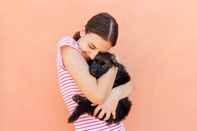 Beautiful girl hugging tight her cute small puppy royalty free stock image