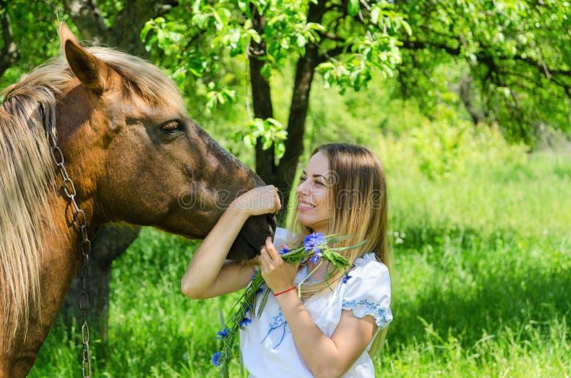 Beautiful girl hugs muzzle of bay peasant horse and laughs royalty free stock photo