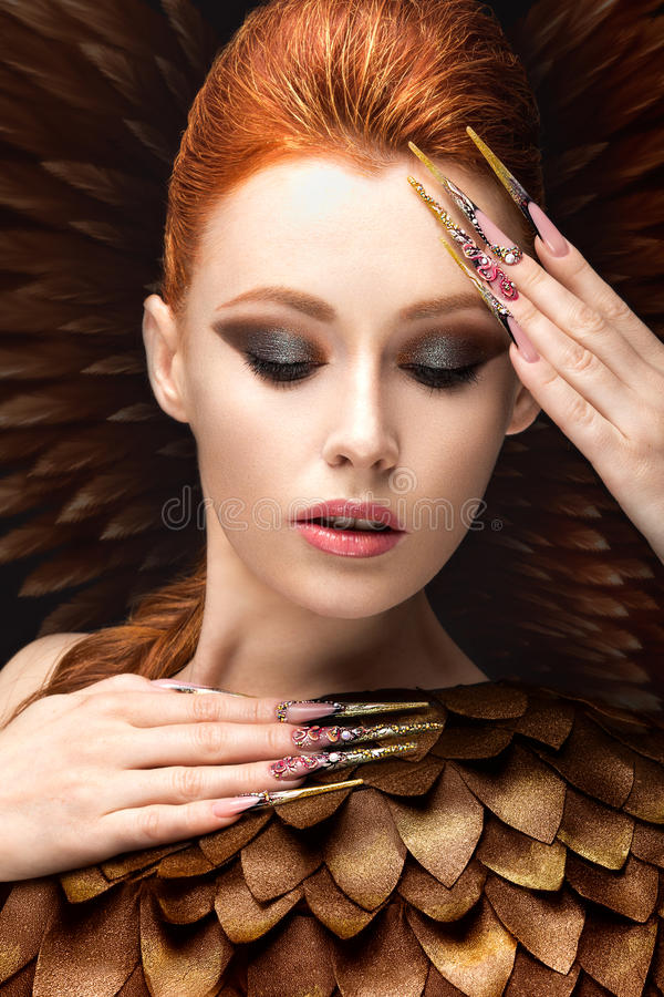 Beautiful girl in the image of the Phoenix with bright makeup, long fingernails and red hair. Beauty face. Picture taken in the studio on a black background royalty free stock image