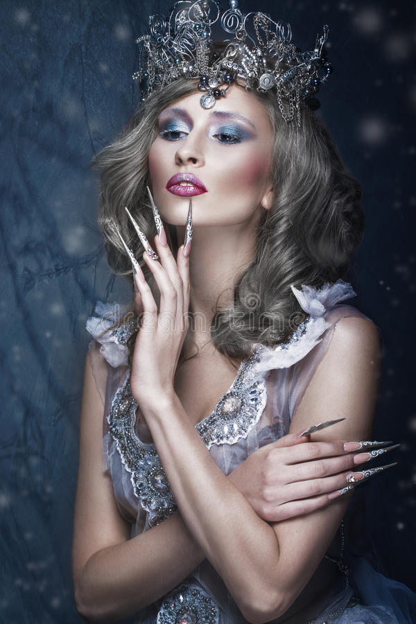 Beautiful girl in image of Snow Queen, creative make-up, transparent dress with crown and long nail art. stock image