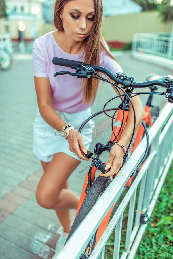 Free Beautiful Girl In A Pink T-shirt At Fence Parking In Summer In The Park. Locks, Locks The Cable With A Code Number Royalty Free Stock Image - 140307576