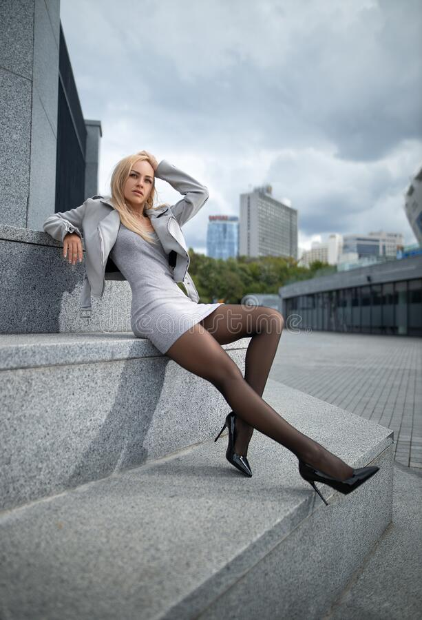 Free Beautiful Girl In Grey Dress With Perfect Legs In Pantyhose And Shoes With High Heels At The City Square Stock Photo - 220061630