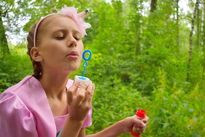 Beautiful girl inflates soap bubbles. Cheerful happy action at the child royalty free stock images