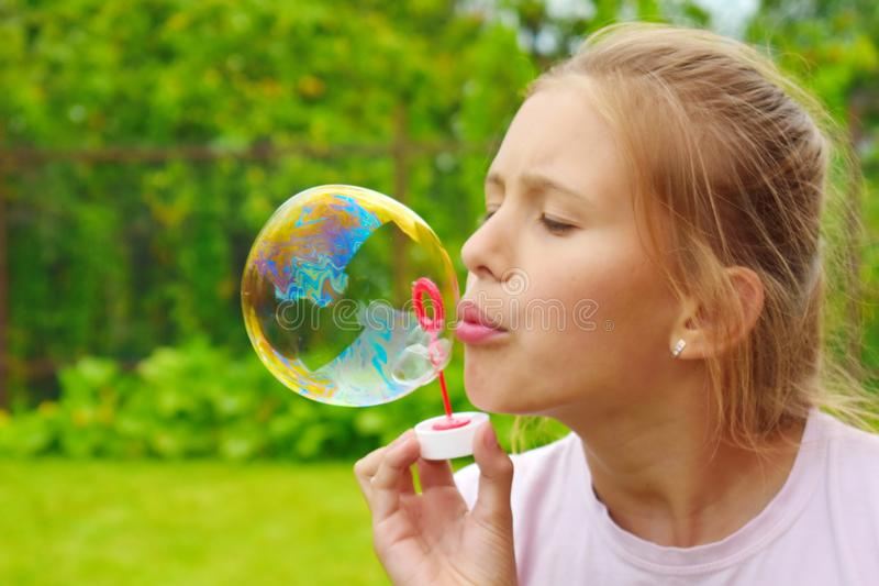 Beautiful girl inflates soap bubbles. Cheerful happy action at the child stock photo