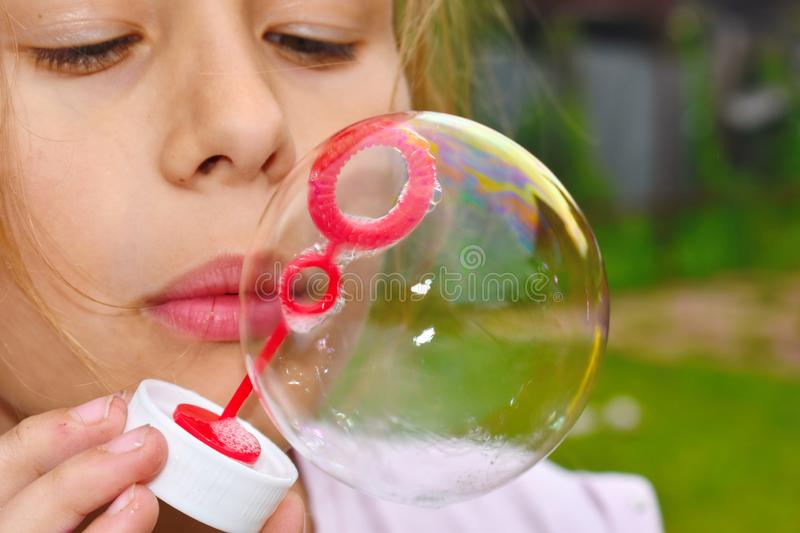 Beautiful girl inflates soap bubbles. Cheerful happy action at the child stock photography