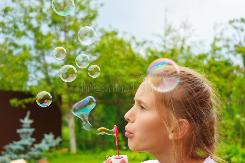 Beautiful girl inflates soap bubbles. Cheerful happy action at the child stock photos