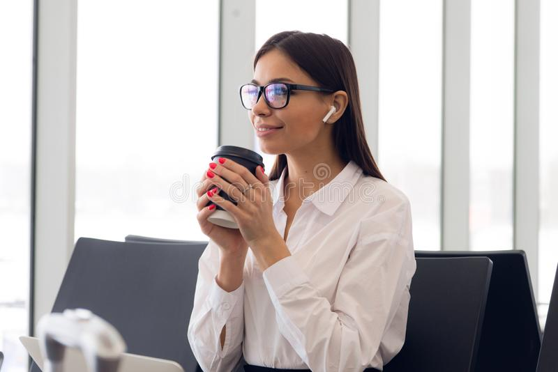 Beautiful girl at international airport, drinking coffee to go while waiting for her flight. Female passenger at stock photo
