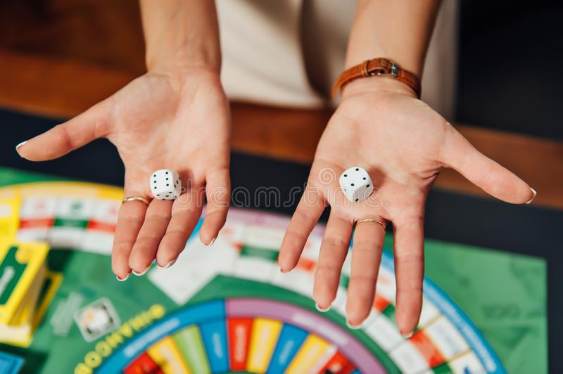 Beautiful girl invites you to play Business Strategy board game.  royalty free stock photography