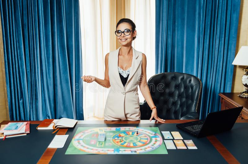 Beautiful girl invites you to play Business Strategy board game.  royalty free stock photo