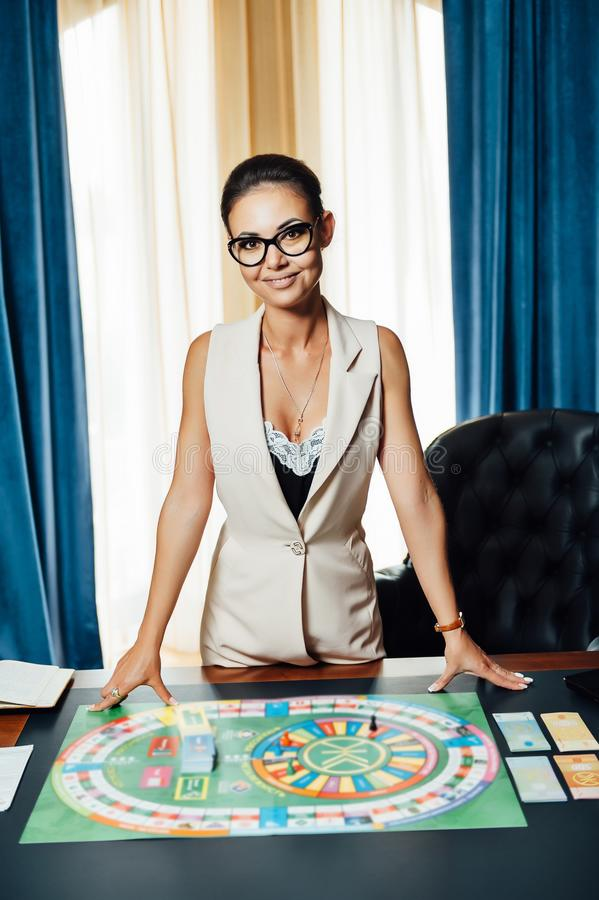 Beautiful girl invites you to play Business Strategy board game.  stock images