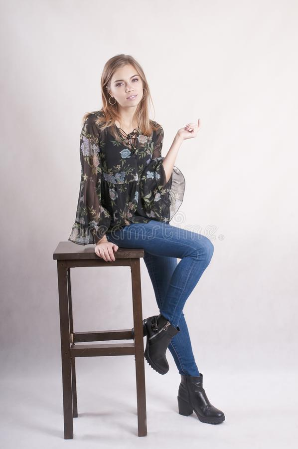 Beautiful girl in jeans sits on a high chair studio lifestyle stock photography