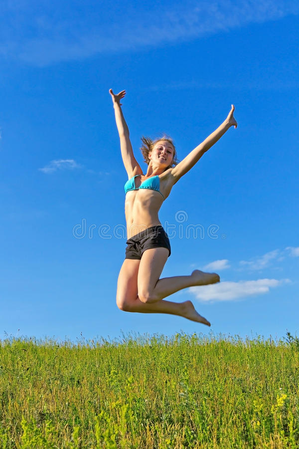 Beautiful girl jumping against the blue sky stock photography