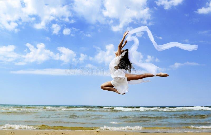 Beautiful girl jumping on the beach stock photos