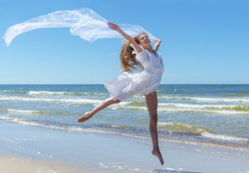 Beautiful girl jumping on the beach stock photo