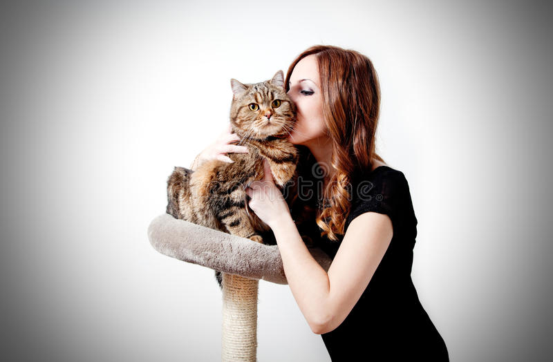Beautiful girl kissing her cat on neutral background. royalty free stock images