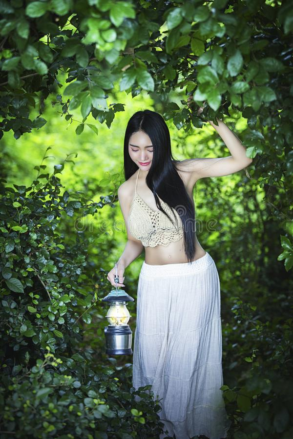 Beautiful girl with lanterns in the forest royalty free stock photography