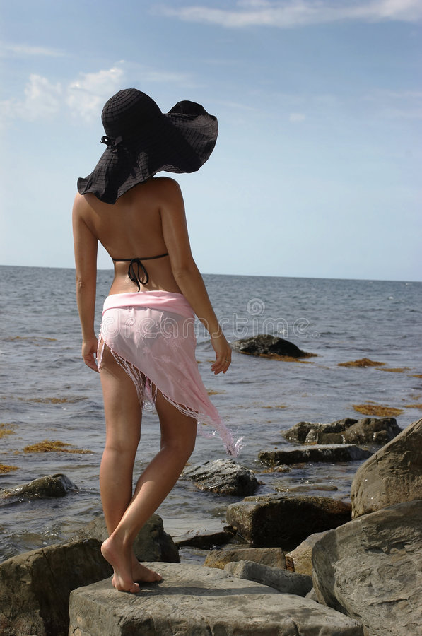 Beautiful girl in the large black hat. Girl in a hat on a stone beach stock photos