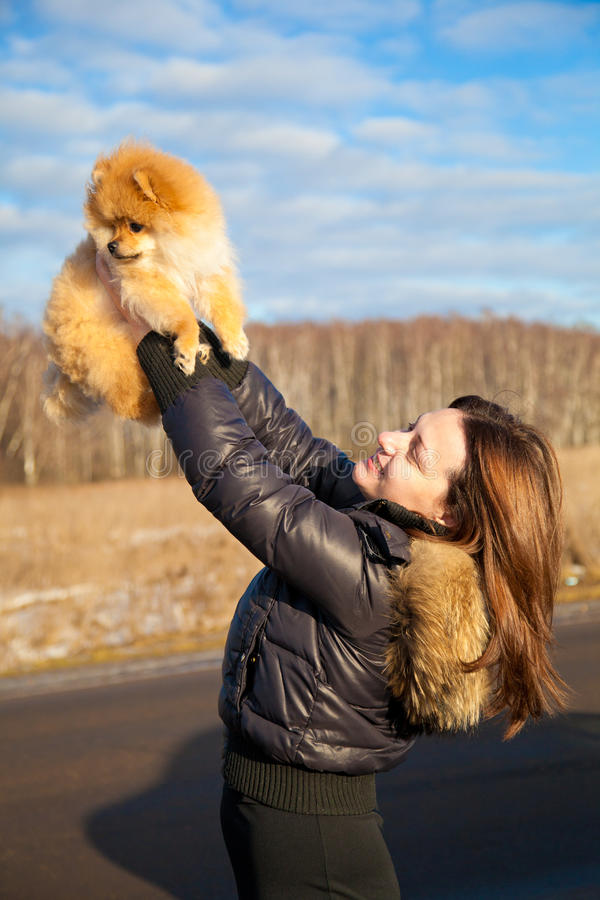 Beautiful girl laughing, picks up the puppy Spitz. royalty free stock photo