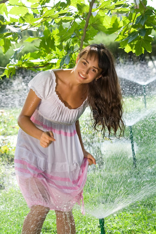 Beautiful girl on the lawn with sprinklers royalty free stock photo