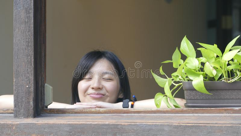 Beautiful girl lay on the winodw enjoy sunlight stock images