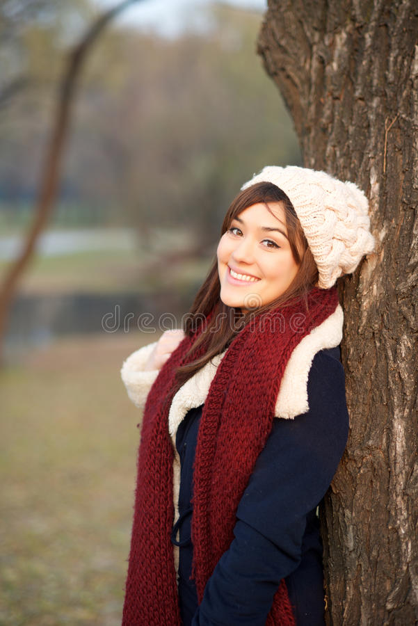 Beautiful girl leaning on a tree royalty free stock photo