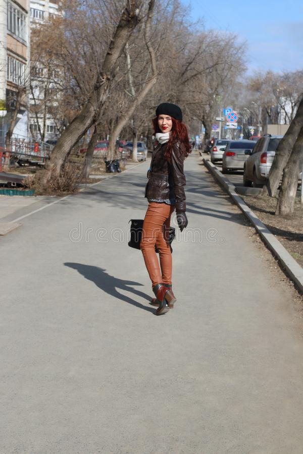 Beautiful girl in leather jacket and beret goes down street royalty free stock photography