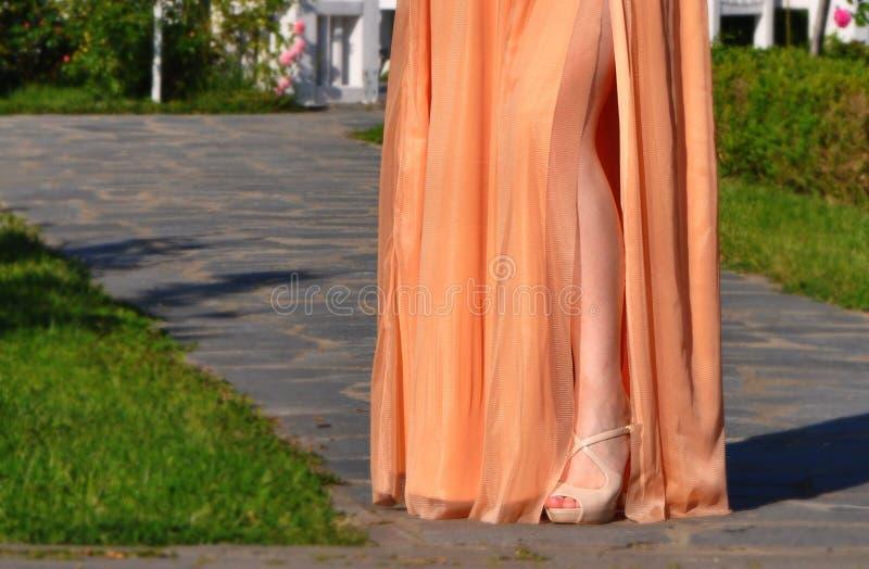Beautiful girl leg in gold long dress stock photo
