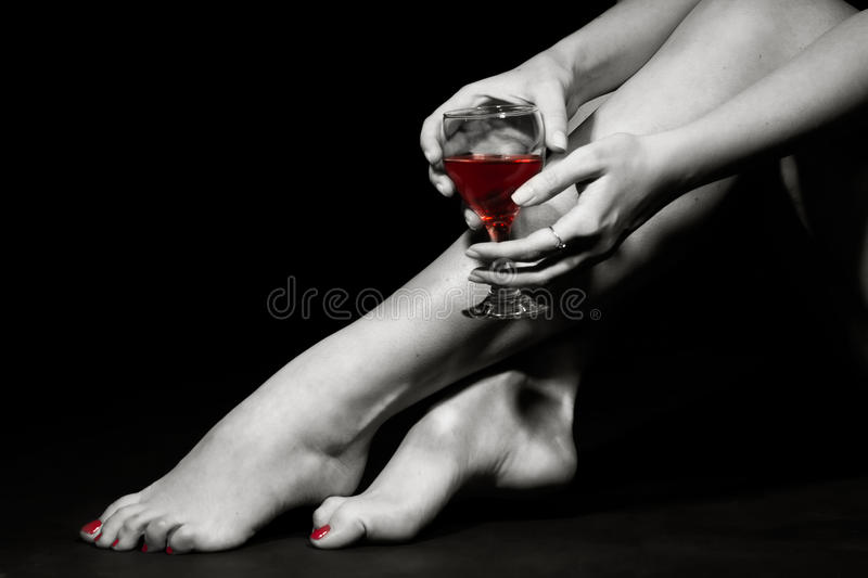 Beautiful girl legs and a glass of red wine. Beautiful girl legs and a glass of alcoholic beverage, black white photo (red wine in glass royalty free stock photography